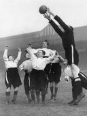 Fulham's goalkeeper stretches to get the ball over the heads of a team of midgets from Earl's Court Circus during a friendly match between the teams