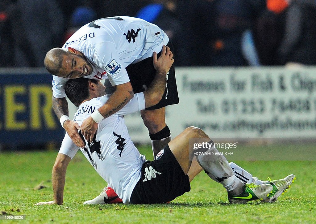 """Fulham's Greek midfielder Giorgos Karagounis (top) and Fulham's Iranian midfielder Ashkan Dejagah (bottom) embrace at the end of their extra-time win during the English FA Cup third round replay football match between Blackpool and Fulham at Bloomfield Road in Blackpool, northwest England, on January 15, 2013. USE. No use with unauthorized audio, video, data, fixture lists, club/league logos or """"live"""" services. Online in-match use limited to 45 images, no video emulation. No use in betting, games or single club/league/player publications."""