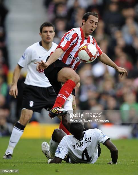 Fulham's John Pantsil continues battling Sunderland's Michael Chopra for the ball despite falling to the ground