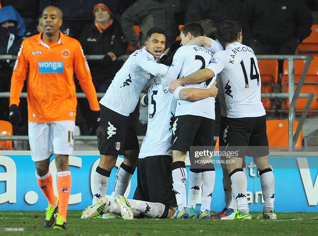 """Fulham's Norwegian defender Brede Hangeland (C) kneels as teammates crowd around him to celebrate his winning goal in extra time during the English FA Cup third round replay football match between Blackpool and Fulham at Bloomfield Road in Blackpool, northwest England, on January 15, 2013. USE. No use with unauthorized audio, video, data, fixture lists, club/league logos or """"live"""" services. Online in-match use limited to 45 images, no video emulation. No use in betting, games or single club/league/player publications."""
