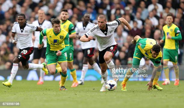 Fulham's Pajtim Kasami competes for the ball with Norwich City's Jonny Howson and Bradley Johnson