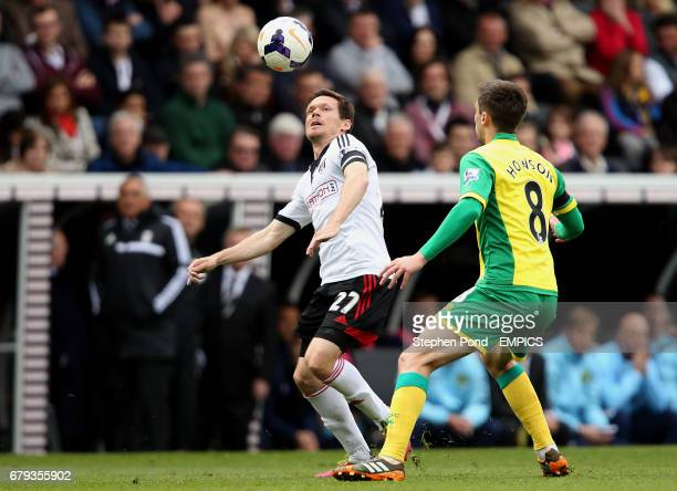 Fulham's Sascha Riether and Norwich City's Jonny Howson compete for the ball