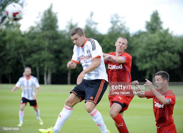 Fulham's Shaun Hutchinson and Rangers' Kenny Miller battle for the ball in the air during the friendly against Rangers FC