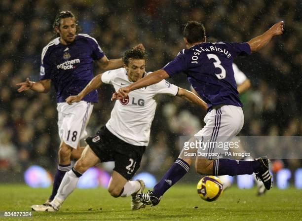 Fulham's Simon Davies and Newcastle United's Sanchez Jose Enrique battle for the ball