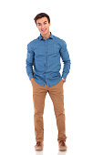 full body picture of a man with hands in pockets smiling for the camera on white background