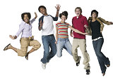 full body portrait of a group of five teenagers as they all jump up in the air