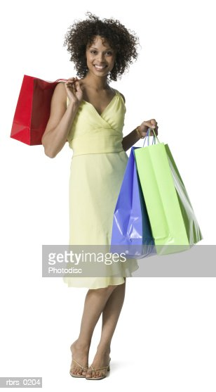full body portrait of a young adult female in a yellow dress as she stands with shopping bags : Stock Photo