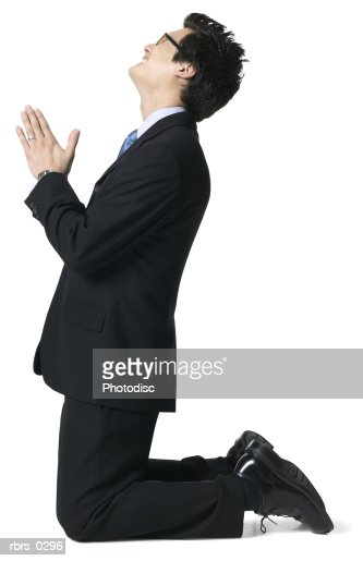 full body portrait of a young adult male in a suit as he gets down on his knees and begs