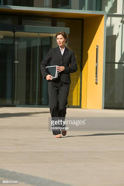 full body portrait of mature businesswoman leaving office building holding files