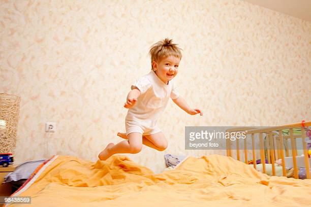 full body portrait of young boy jumping on bed