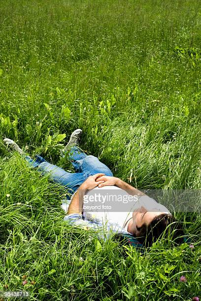 full body portrait of young man dozing in grass
