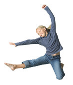 full body shot of a blonde female child as she jumps and kicks through the air