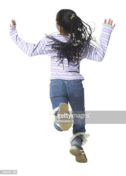 full body shot of a female child as she runs and jumps playfully through the air