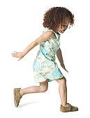 full body shot of a female child as she runs forward playfully