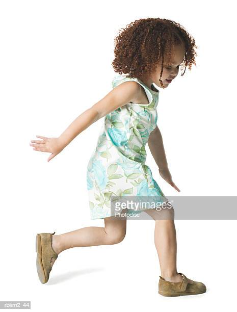 full body shot of a female child as she runs forward playfully