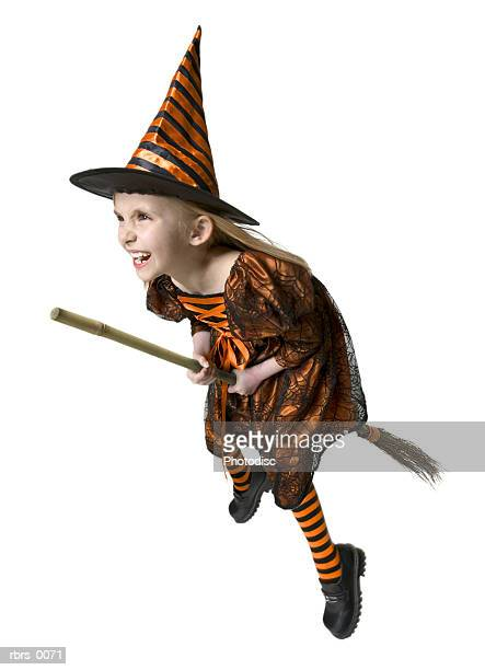 full body shot of a female child dressed as a witch for halloween as she rides a broomstick