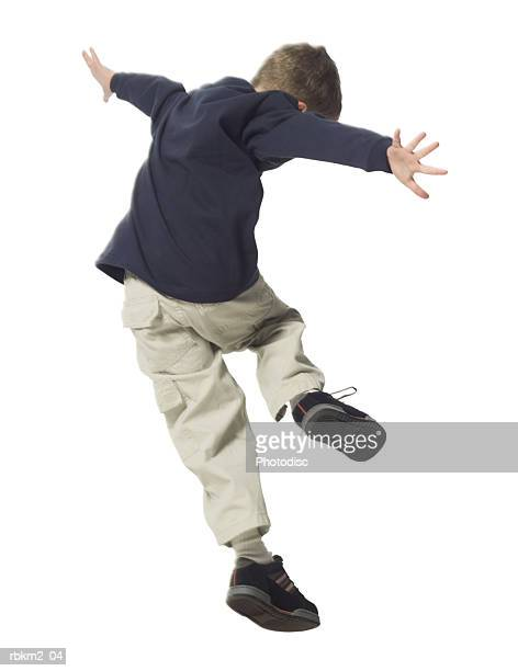 full body shot of a male child as he skips and dances through the air