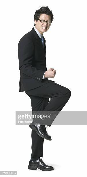 full body shot of a young adult business man as he celebrates a job well done