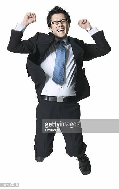full body shot of a young adult business man as he jumps up in celebration