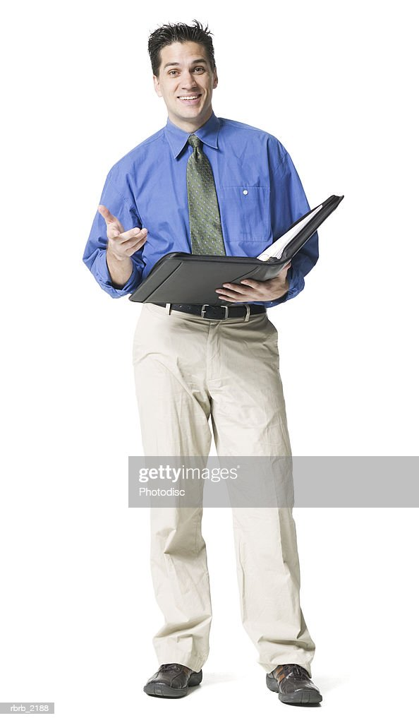 full body shot of a young adult business man in a blue shirt and tie as he lectures form his notebook : Foto de stock