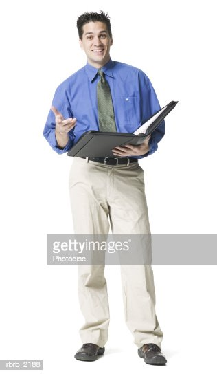 full body shot of a young adult business man in a blue shirt and tie as he lectures form his notebook : ストックフォト