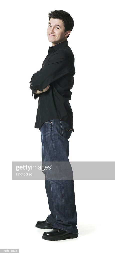 full body shot of a young adult male as he folds his arms and smirks : Stock Photo