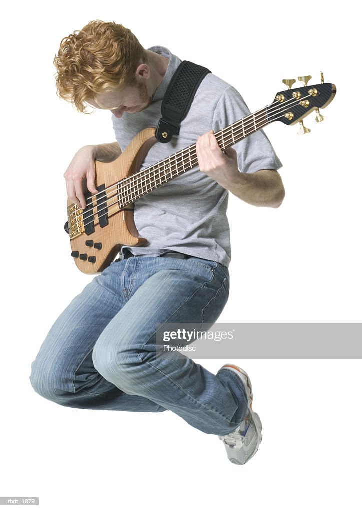 full body shot of a young adult male in a grey shirt as he jumps up with his guitar