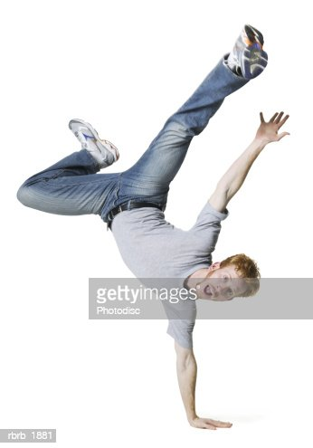 full body shot of a young adult male in a grey shirt as he jumps up and balances on one hand : Stock Photo