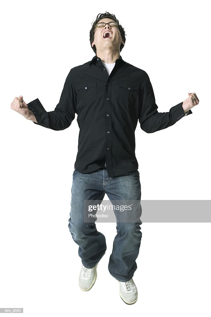 full body shot of a young adult man in a black shirt as he jumps and throws back his head : Stock Photo