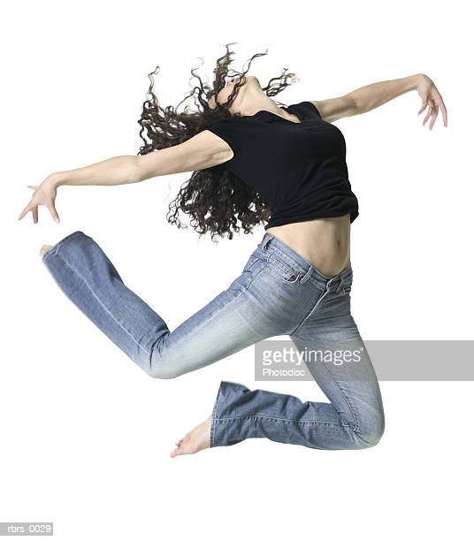full body shot of a young adult woman as she energetically jumps up in the air