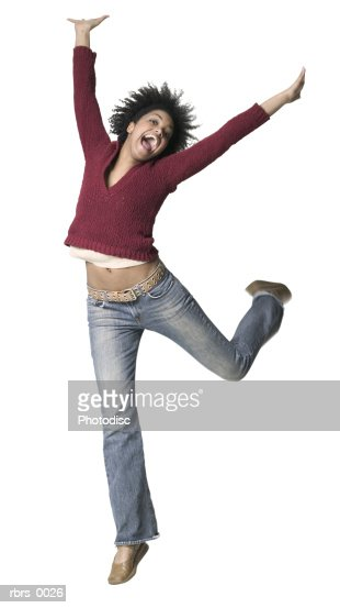 full body shot of a young adult woman as she playfully jumps and throws up her arms : Stock Photo
