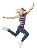 full body shot of a young adult woman in a workout outfit as she runs and jumps through the air