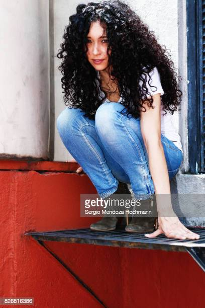 Full body shot of a young woman with very curly hair crouching on a rooftop in Mexico City