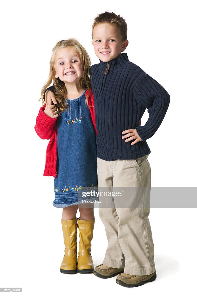 full body shot of two children as the boy puts his arm around the girl and they smile : Stock Photo