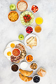Filling breakfast with eggs sunny side up, sausages, bacon and mushrooms with fruits and vegetables, breads and juice on the grey white table, top view, copy space, vertical, selective focus
