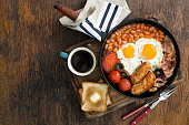 Full English breakfast with sausages, bacon, fried eggs, beans, toast and cup of coffee on wooden table with copy space, top view