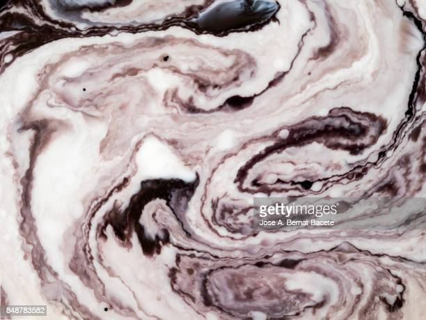 Full frame of abstract shapes and textures formed on a white liquid background
