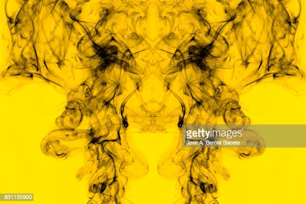 Full frame of forms and figures of smoke of color gray and black in ascending movement , on a vintage yellow background