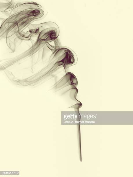 Full frame of forms and figures of smoke of color gray in ascending movement on a vintage yellow background
