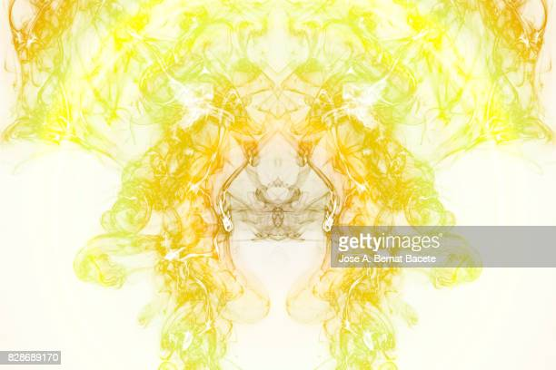 Full frame of forms and figures of smoke of color green and yellow in ascending movement , on a white background