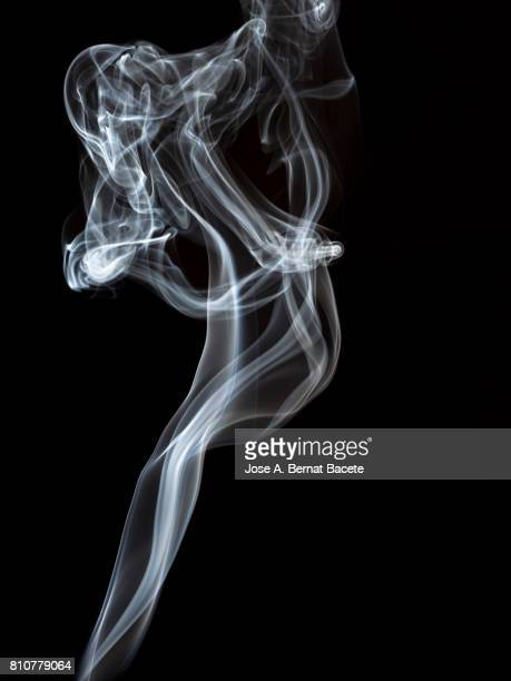 Full frame of forms and figures of smoke of color white in ascending movement produced, by an explosion on a black background