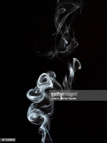 Full frame of forms and figures of smoke of color white in ascending movement on a black background
