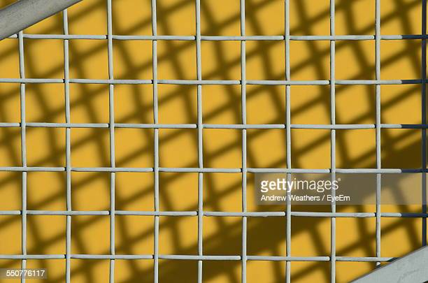 Full Frame Shot Of Metal Fence Against Yellow Wall