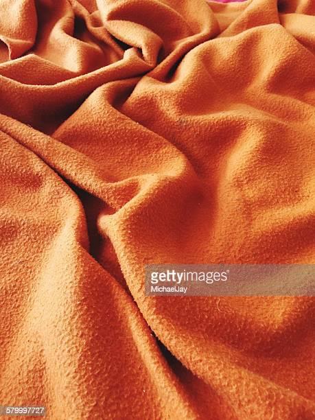 Full Frame Shot Of Orange Crumpled Blanket At Home