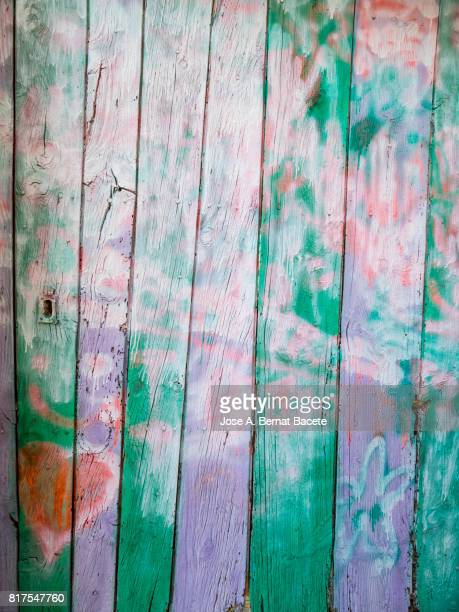 Full Frame  textures of from a wooden door abandoned painted in various colors by graffiti and closed with a chain