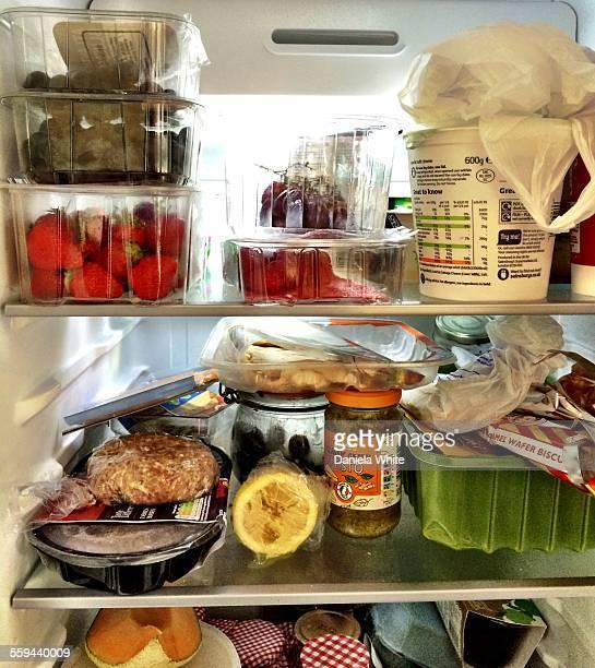 Full fridge shelves Fruits lemon Charcuterie Burger Yoghurt Berries