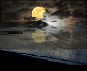 full yellow harvest moon coming up upon the horizon over water leaving an amazing beautiful reflection in the water