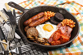 full irish breakfast with fried egg, sausages, black pudding, white pudding, baked beans, bacon, tomato and grilled mushrooms in a cast iron pan