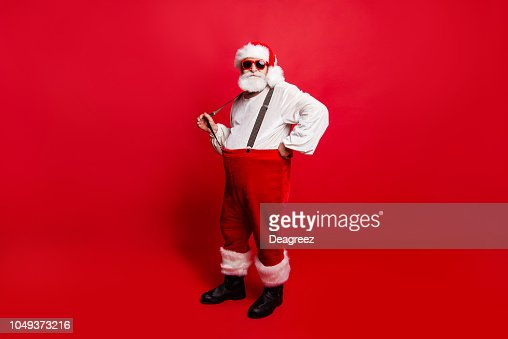 Full length body size of nice calm peaceful Santa pulling suspender preparing to feast festive party promo sale discount isolated over red background : Foto de stock