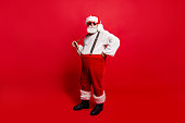 Full length body size of nice calm peaceful Santa pulling suspender preparing to feast festive party promo sale discount isolated over red background